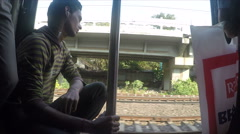 Man sitting by open train door during ride. Stock Footage