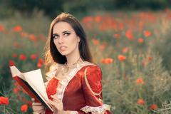 Beautiful Princess Reading a Book in Summer Floral Landscape Stock Photos