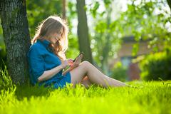 Pretty young caucasian woman  sitting outside under a tree talking on smartphone - stock photo