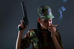 Female soldier in camouflage uniform with gun and cigar smoke Stock Photos