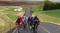 Stock Video Footage of Group of cyclists riding up a hill