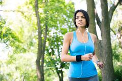 Sporty young woman running outdoors Stock Photos
