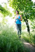 Cute fitness woman running in park - stock photo