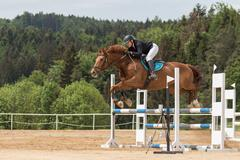 Stock Photo of Jumping horsewoman in black jacket. Side view.