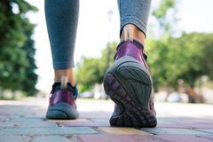 Footwear on female feet running on road - stock photo