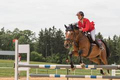 Closeup side view of  horsewoman in red jacket jumping - stock photo