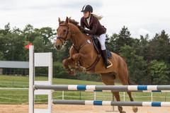 Closeup view of young blonde horsewoman jumping - stock photo