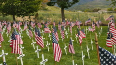 Pan- A field of crosses with flags waving for veterans buried in cemetery Stock Footage
