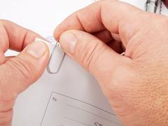 Paper clip in hands - stock photo