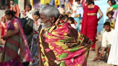 Indian man covered in blanket talking at the street in Varanasi. Stock Footage