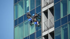 Industrial climbers washing windows  time lapse Stock Footage