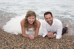 Newly married couple lying on the beach Stock Photos