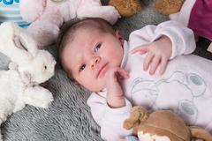 Close up of new born baby with cute expression - stock photo