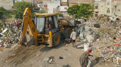 Excavator clearing waste at garbage dump in India Stock Footage