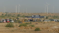 Windmill park behind petrol station in Rajasthan desert, India Stock Footage