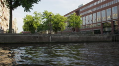 Tracking shot of downtown Amsterdam along the canal in Netherlands with lens Stock Footage