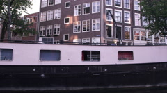 Sped-up video of buildings on a street and houseboats along the canal in Stock Footage