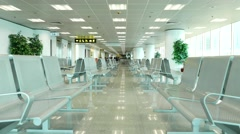 Empty seats in lounge area, people walking far away, terminal hall - stock footage