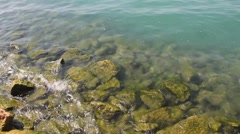 Waves hitting Moss-Covered Rocks in Italian Lake Stock Footage