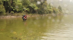 Man crossing a waist deep river with backpack Stock Footage