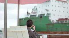 Man Sitting Under Beach Umbrella with Freighter In Background Stock Footage