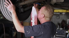 Slow motion shot of a mechanic the front undercarriage of a car. Stock Footage