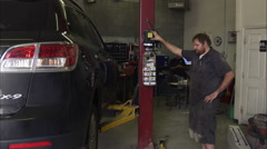 Slow motion of a scruffy mechanic in a garage. Stock Footage
