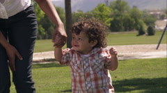 Slow handheld shot of an Indian mother and her son walking in the park. - stock footage