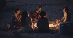 Beach Party at sunset with bonfire and roasting marshmellows with friends Stock Footage