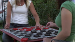 Stock Video Footage of Slow motion tilt shot of two women playing checkers in a garden