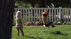 Slow motion handheld shot of a child swinging on a tree swing while another one Stock Footage