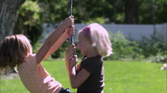 Slow motion pan of two girls sharing a tree swing Stock Footage