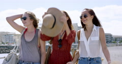 Three young women tourists on summer vacation girl friends walking on beach Stock Footage