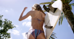 Rear view of Surfer girl walking on beach with surfboard low angle of surfing Stock Footage