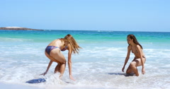 Beautiful girls rinsing off sand in water at beach on tropical vacation wearing Stock Footage