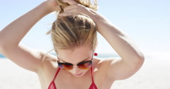 Close up portrait of beautiful young teenage girl tying up hair on windy day on - stock footage