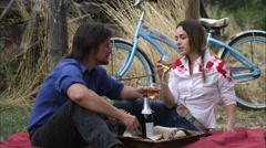 Slow tracking shot of a young couple enjoying white wine at an outdoor picnic Stock Footage