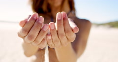 Close up of pretty girl pouring sand running through fingers slow motion at the Stock Footage