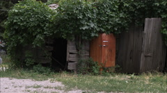 Static shot of old rusty ice box along a fence. Stock Footage