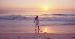 Beautiful woman wearing white dress walking along shore line on  beach at sunset Stock Footage