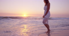Beautiful woman lifting white dress walking along shore line on  beach at sunset Stock Footage