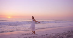 Free happy woman spinning arms outstretched enjoying nature dancing on beach at - stock footage