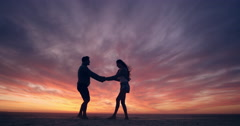 Happy couple dancing on beach enjoying honeymoon in nature at sunset silhouetted Stock Footage