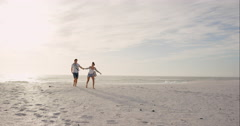 Young couple holding hands walking towards sunset on empty beach - stock footage