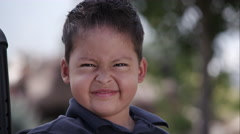 Little Latino boy sitting in a wheelchair in front of a rock and flower garden Stock Footage