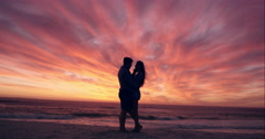 Happy couple kissing on beach at sunset silhouette in love dating on honeymoon - stock footage