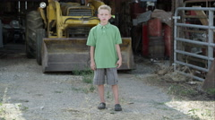 Slow motion push of boy with cleft lip standing in front of tractor. Stock Footage