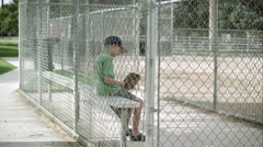Slow motion push of boy sitting in dugout behind chain link fence. Stock Footage