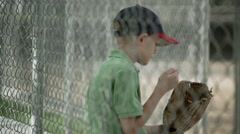 Slow motion rack focus of boy sitting in dugout behind chain link fence. Stock Footage