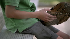 Slow motion of boy holding baseball mitt then setting it down next to him on Stock Footage